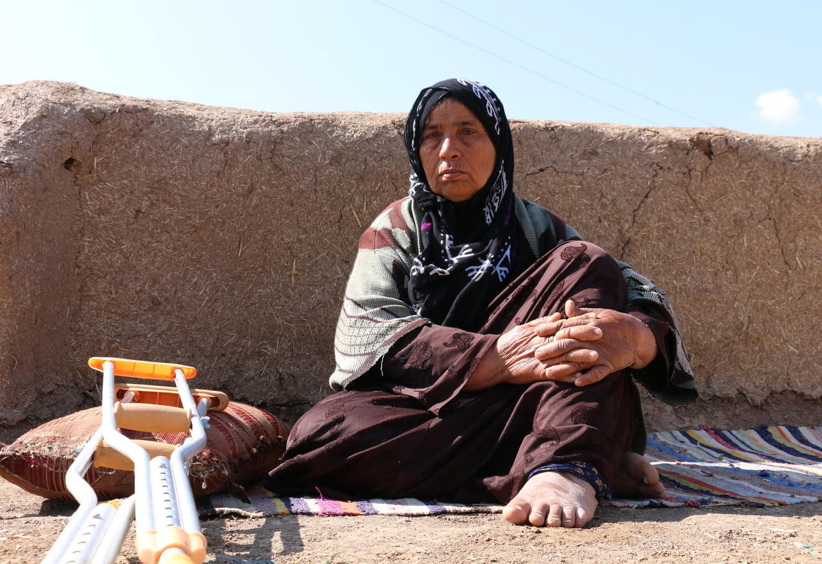 Miriam, 65, sits on a mat outside her home in Syria to get some fresh air