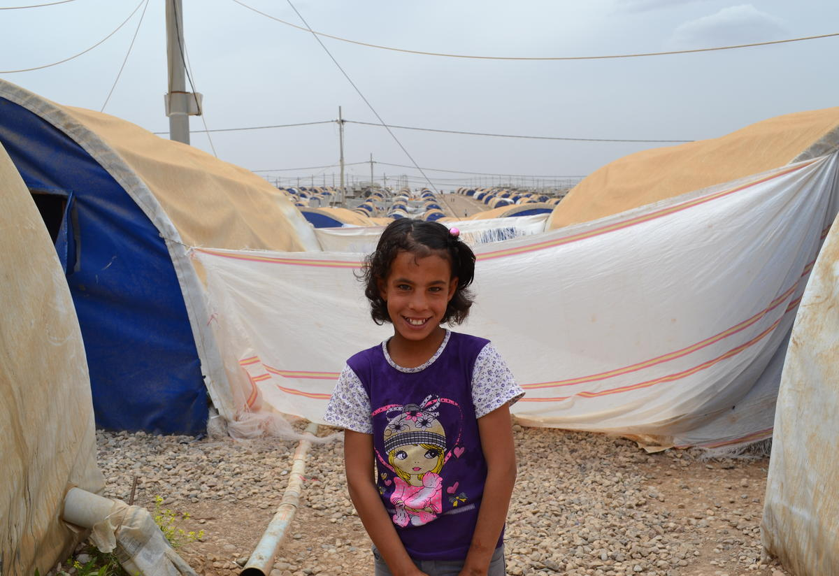 Eleven-year-old Farah outside her family's tent in Nargazilia camp, Iraq