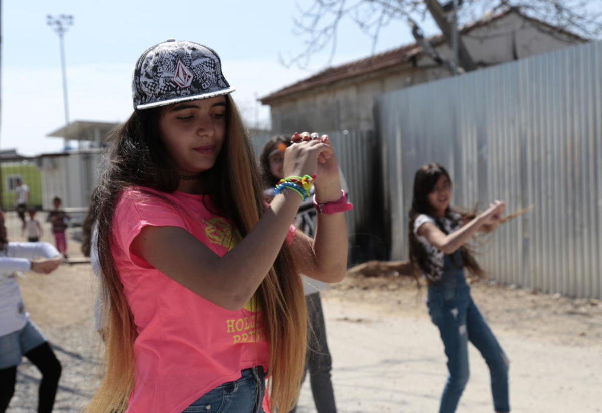 Rolian, 16, shows off her dance moves at Eleonas refugee camp in Greece.