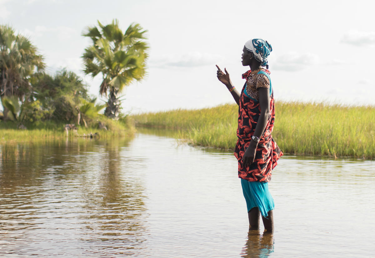 A woman stands in a swamp in Unity State, South Sudan