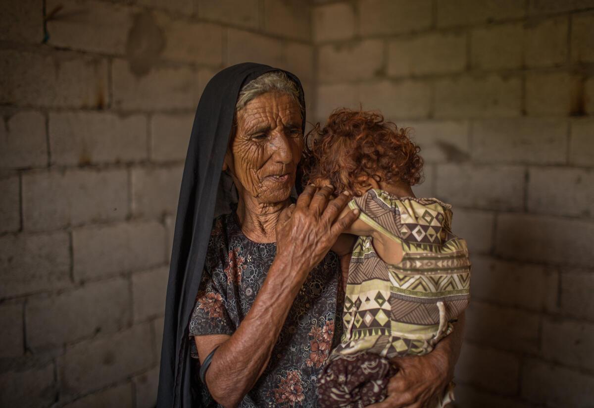 Fatma Salim Qebas holds her toddler granddaughter inside their home