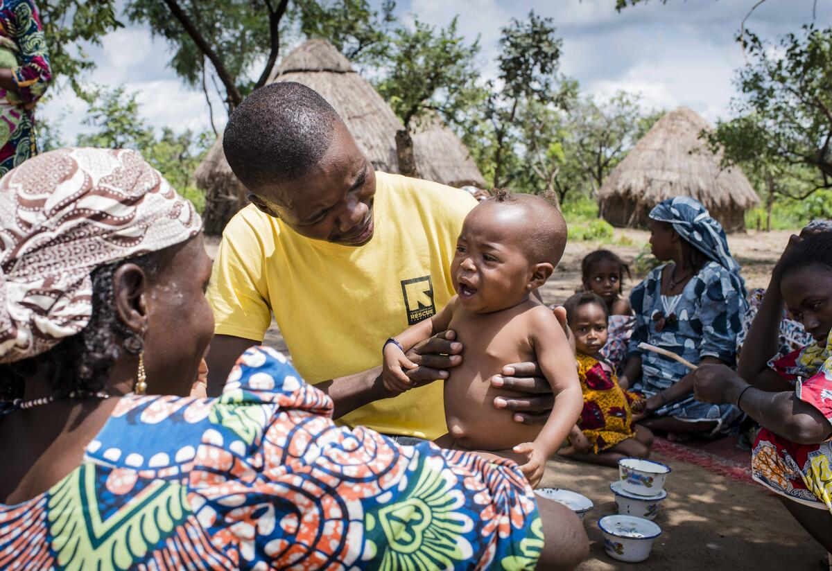 An IRC health worker examines a young child suffering from malnutrition as people return to their village after fleeing fighting.