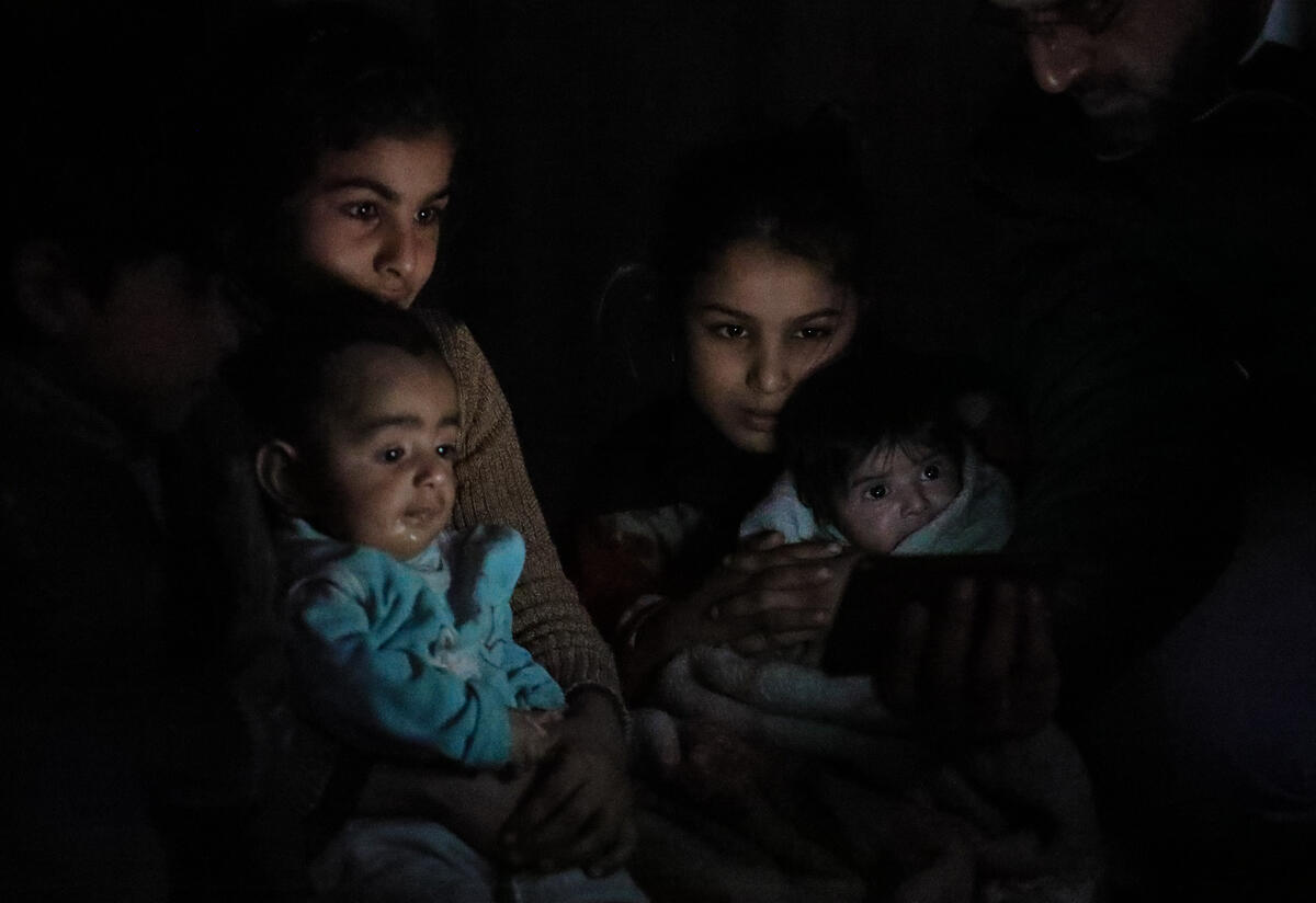 A family huddles in the dark in their basement shelter in East Ghouta, Syria