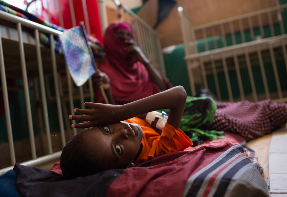 A young boy lies on a cot in the Mogadishu hospital where he is being treated for malnutrition