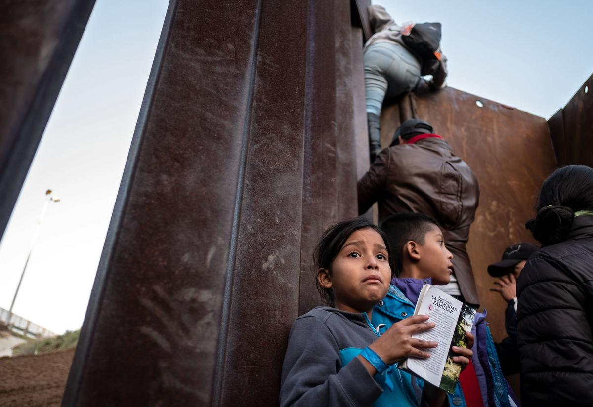 A Central American girl holds a book as others traveling in a caravan climb the Mexico-U.S. border fence in an attempt to cross to San Diego County.