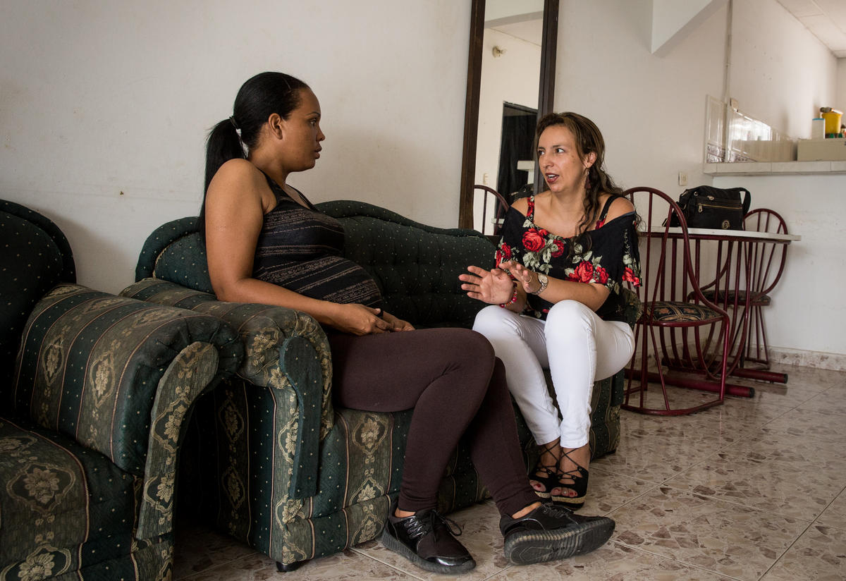 Cibel and an IRC nurse, Diana, sit on a sofa and talk.