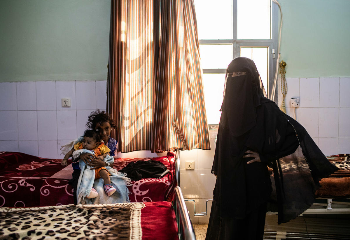 A woman and children at an IRC supported hospital in Al Buraiqa District on the outskirts of Aden, Yemen