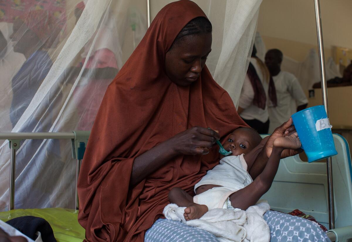 A mother feeds her malnourished baby therapeutic food with a spoon in an IRC health clinic in Nigeria.