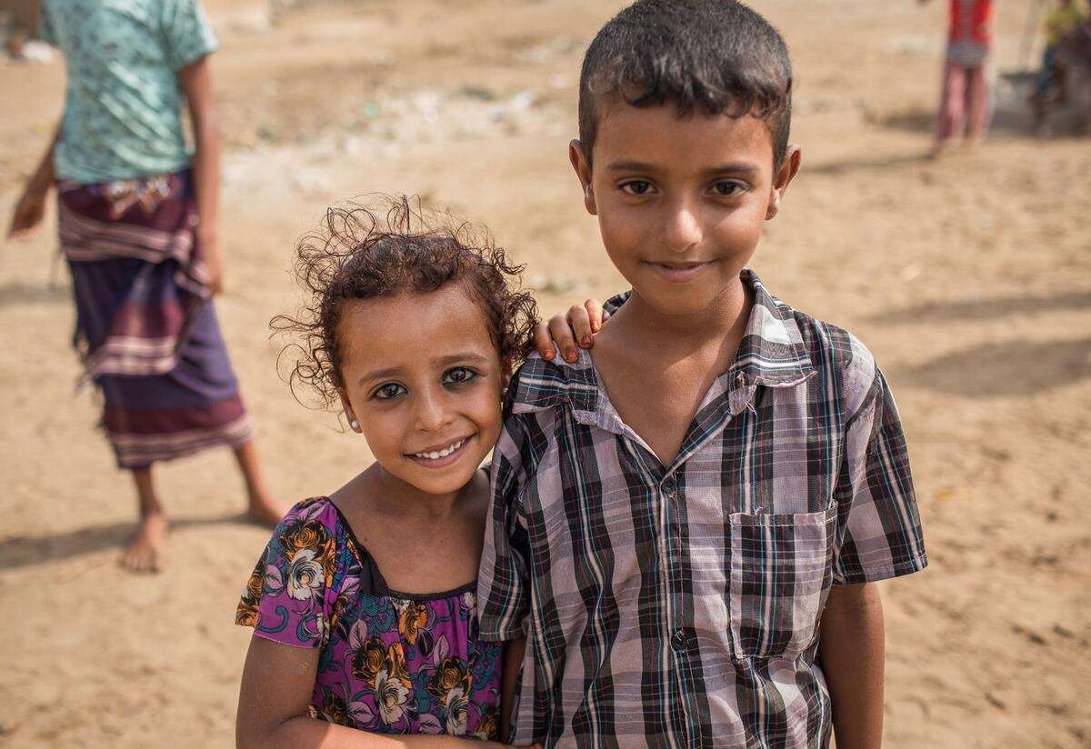 A girl and boy stand in front of their home in Al Buraiqeh, a remote village on the outskirts of Aden, Yemen, where IRC health teams provide care for malnutrition,