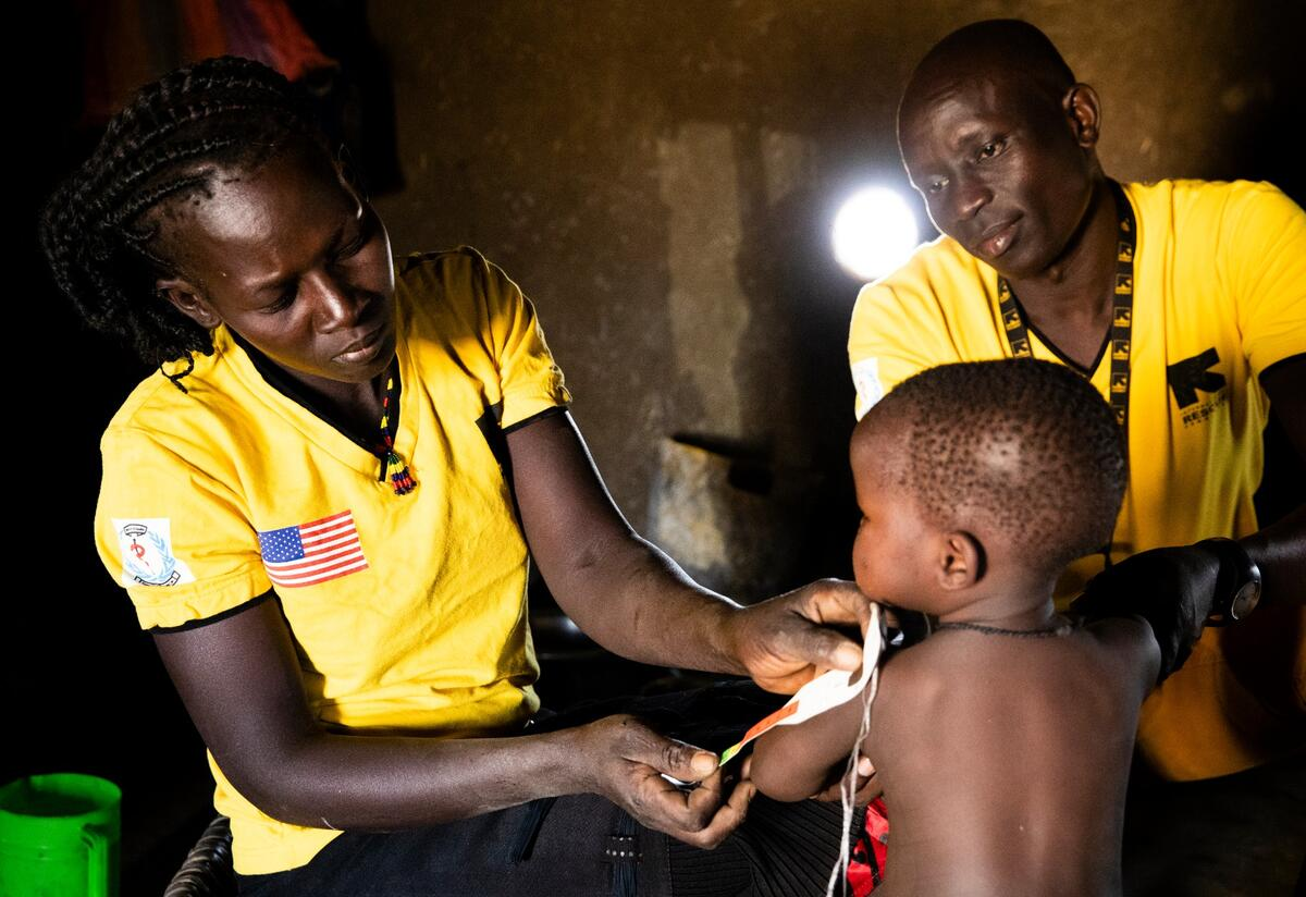 Health workers in South Sudan measure a toddler's arm for signs of malnutrition.