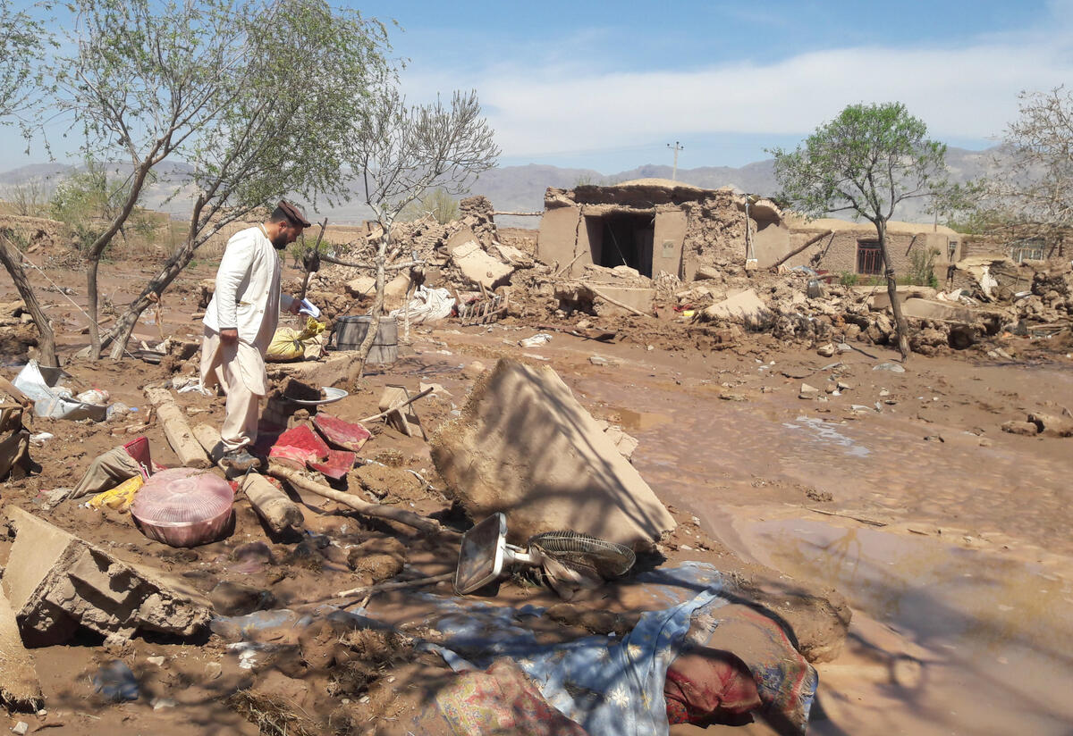 An IRC staff  member walks through the flood hit village of Shadi Bara, Herat, Afghanistan