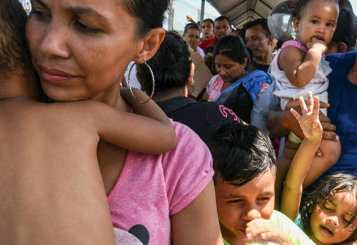 A Central American family waits to cross a border on their way to seek asylum in the U.S.