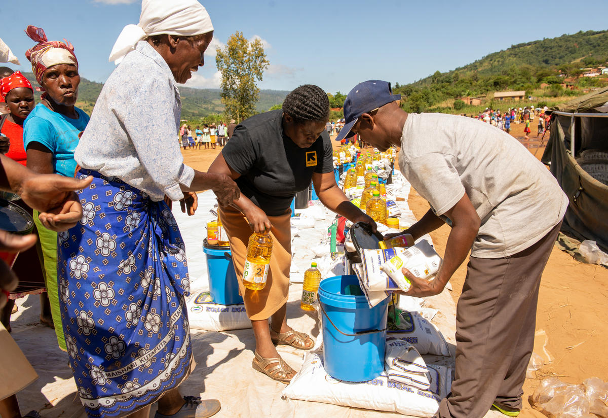 tow IRC aid workers help a woman pack a bottle of cooking oil and other food aid and emergency supplies in Machongwe, Zimbabwe