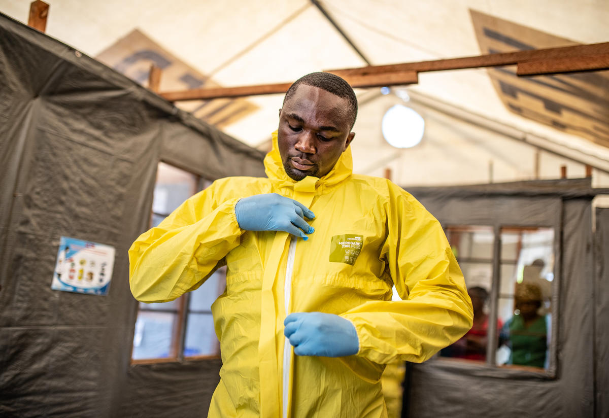 A health worker in the Democratic Republic of Congo puts on his jumpsuit and other protective gear to care for potential Ebola patients.
