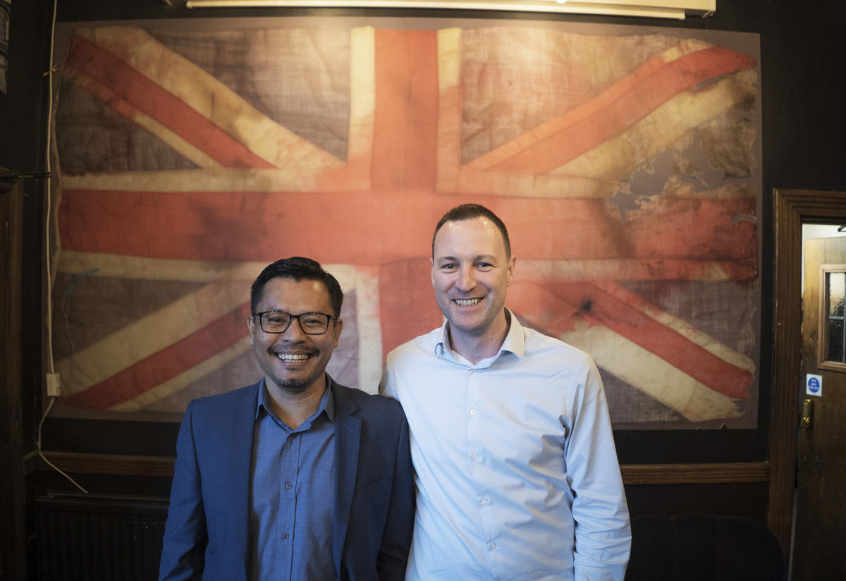 Warren (left) and Darren stand in front of a Union Jack flag in London