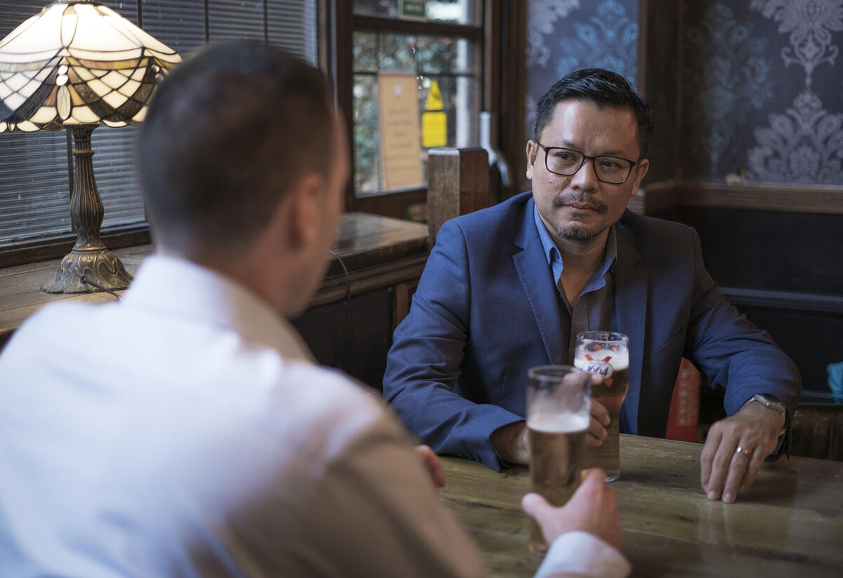 Darren and Warren talk at a pub table over over pints of beer