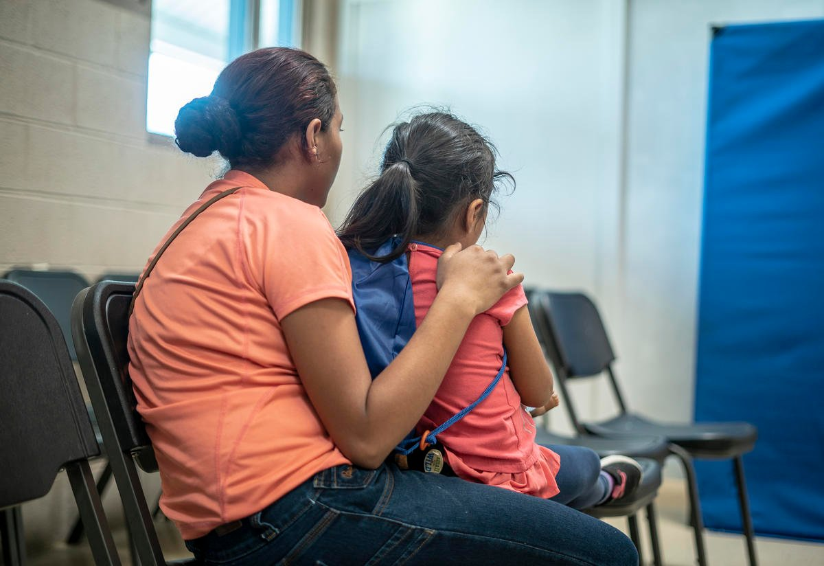 Emilia sits with her arms around four-year-old Lauda in a shelter in Phoenix, Arizona for asylum-seeking families who were released from detention at the U.S. border