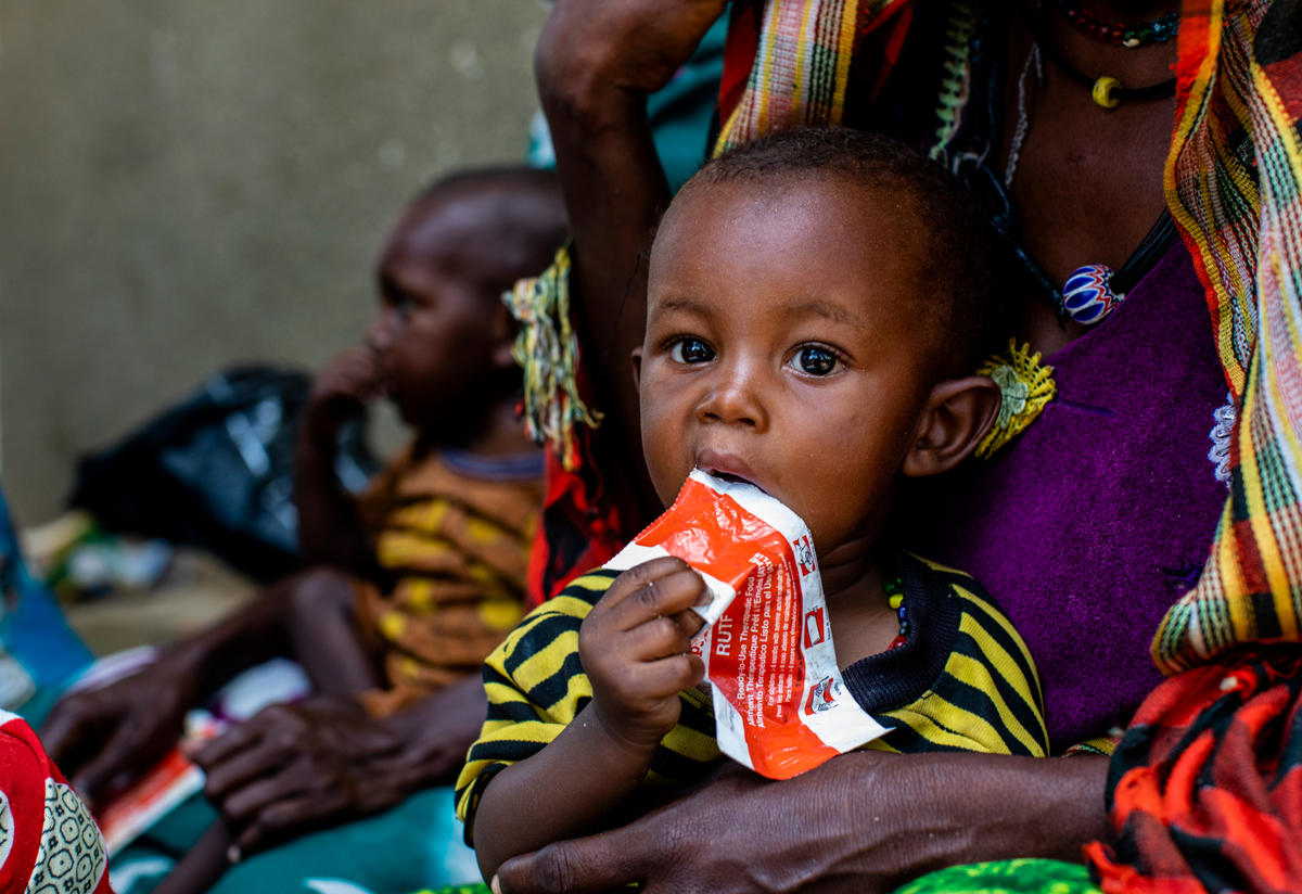 A young boy in his mother's lap eats a peanut-based nutrition supplement after being diagnosed with acute malnutrition at an International Rescue Committee supported health center in Chad.