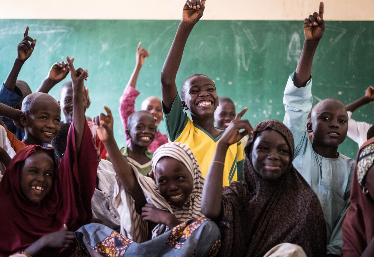 Students excitedly raise their hands in class at an International Rescue Committee supported school in Nigeria.