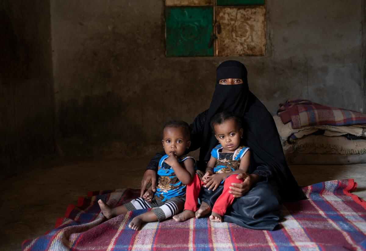 Fulla sits with her young twin daughters, who received medical help from the International Rescue Committee when they were diagnosed as acutely malnourished.