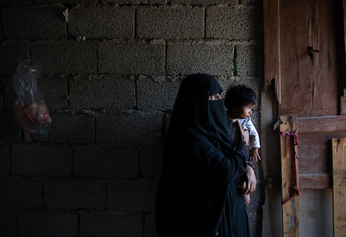 Adeeyah Aholds her toddler daughter Salaman in the dark kitchen of their temporary home in Yemen. The family received assistance from the International Rescue Committee.