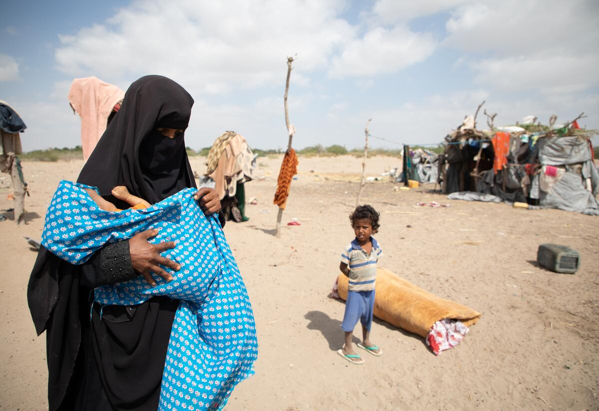 Nadia holds her baby son wrapped in a blanket outside her makeshift home in Yemen. The family received medical and nutrition assistance from the International Rescue Committee.