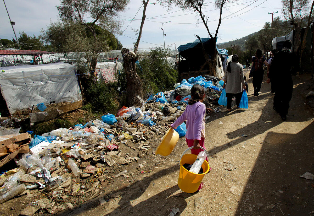 A young girl walks past tents and trash in an overcrowded refugee center