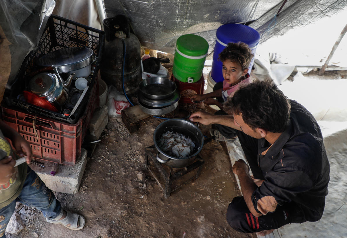 Naeem, 24, and his family around a cooking fire in their makeshift shalter in northern Idlib, where the IRC is assisting uprooted Syrians.