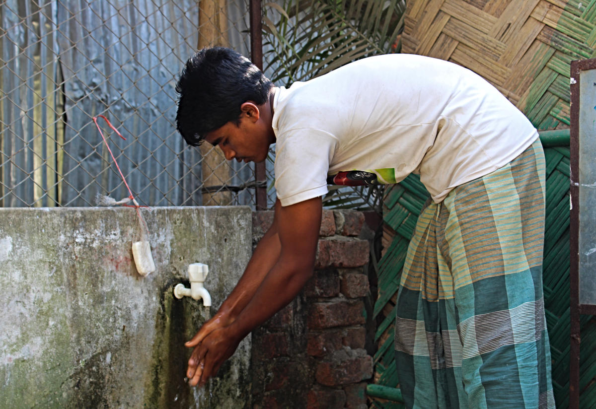 A young refugee washes his hands at a crowded refugee camp in Cox's Bazar, Bangladesh, where the IRC is providing support to Rohingya refugees from Myanmar.