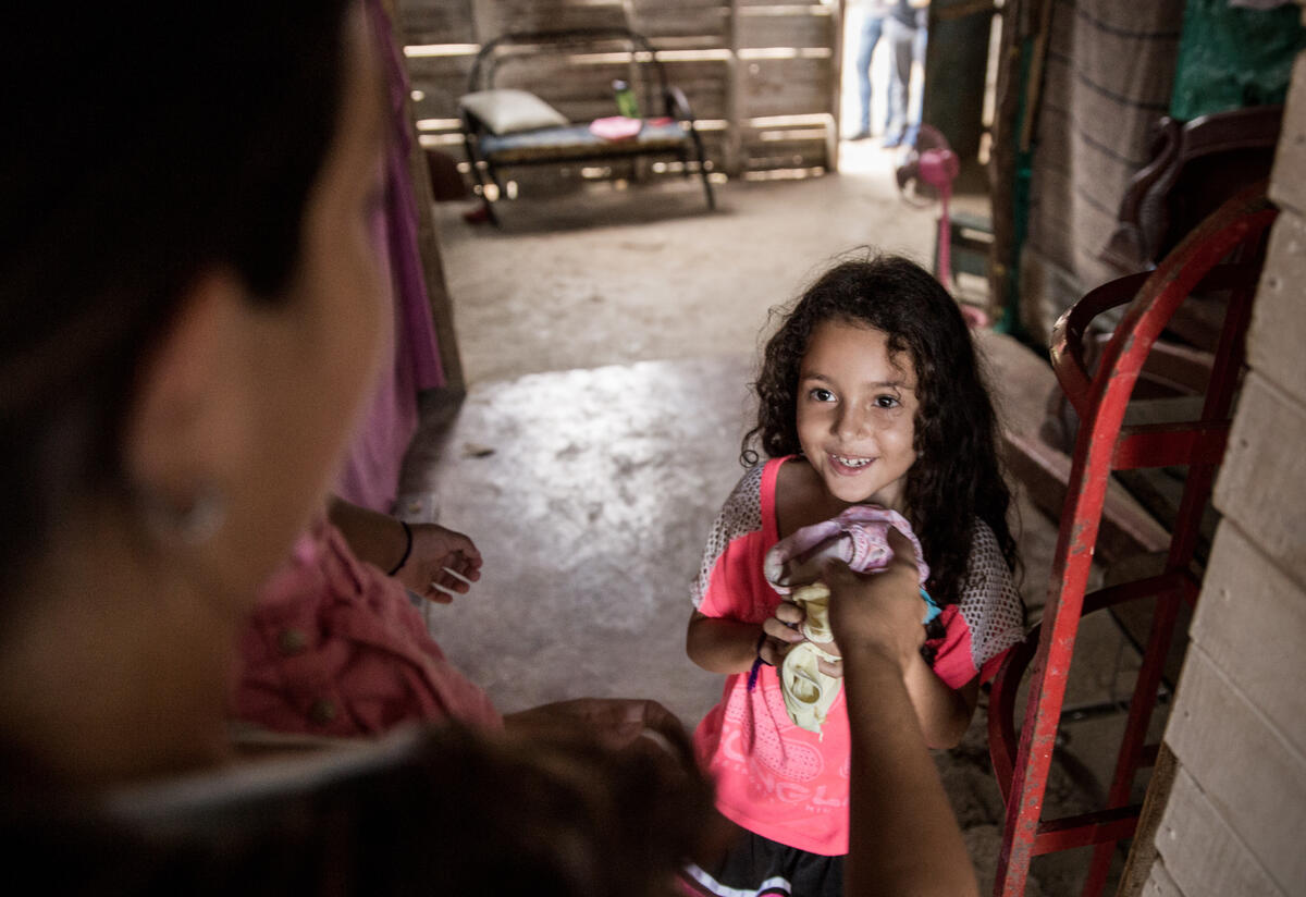 Venezuelan refugee Andrea and her young daughter in their homebuilt of scrap wood in Cucuta, Colombia