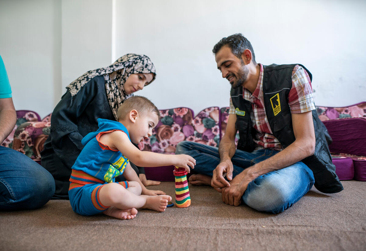 Anas, an IRC Reach Up & Learn volunteer and Syrian refugee plays stacking rings with 2-year-old Rashid at his family's home.