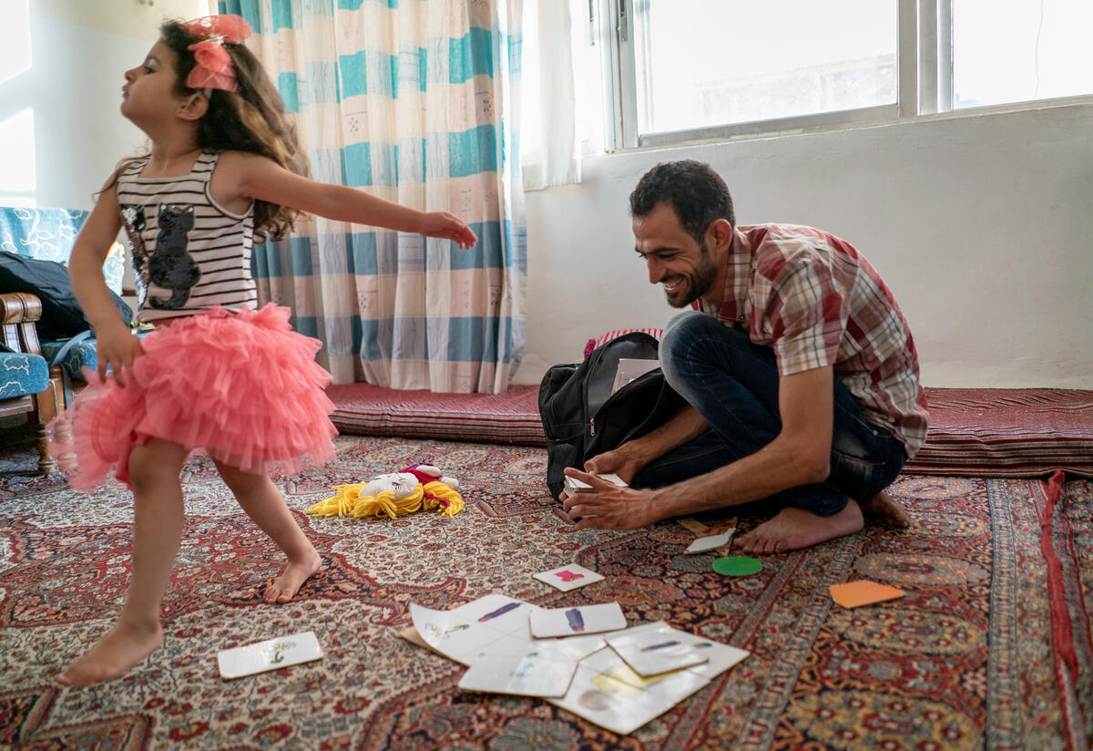 Anas, an IRC Reach Up & Learn volunteer and Syrian refugee, plays with his daughter Maria, 4 years old, at their home in Mafraq Jordan.