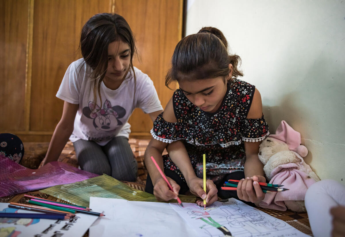 Two young sisters in Sinjar, Iraq sit on the floor coloring in an activity book