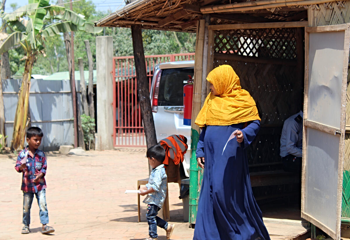 Sakera and her sons outside the outpatient area of the IRC primary health care center in Cox's Bazar