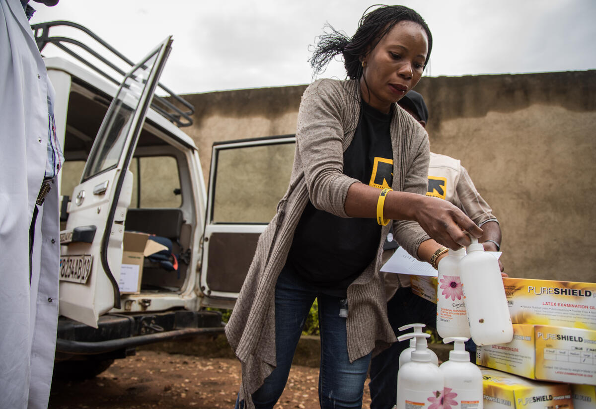 Dr. Sylvie Musema Ngimba of the IRC unloads personal protective eqipment and sanitizer from a 4-wheel-drive vehicle.