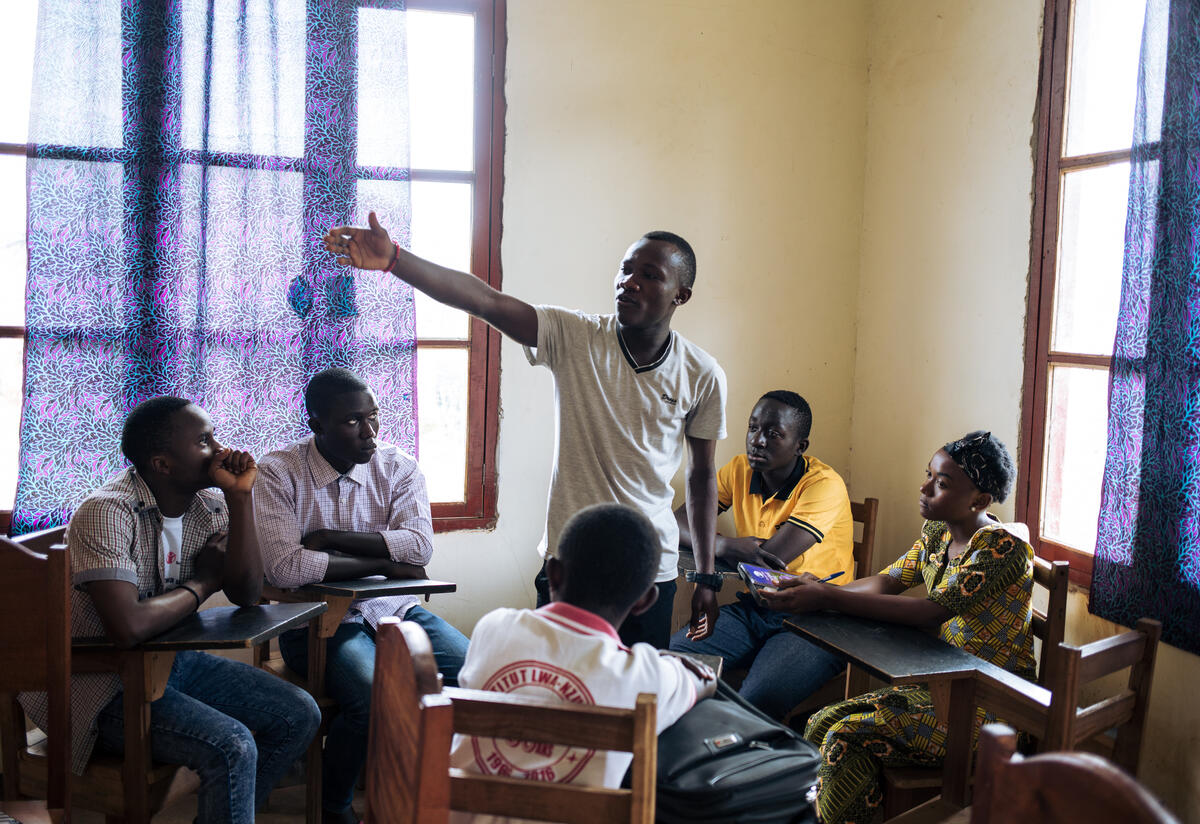 Youth leader Benjamin stands inside a circle of seated teenagers, pointing as he gives an IRC-supported training on Ebola.