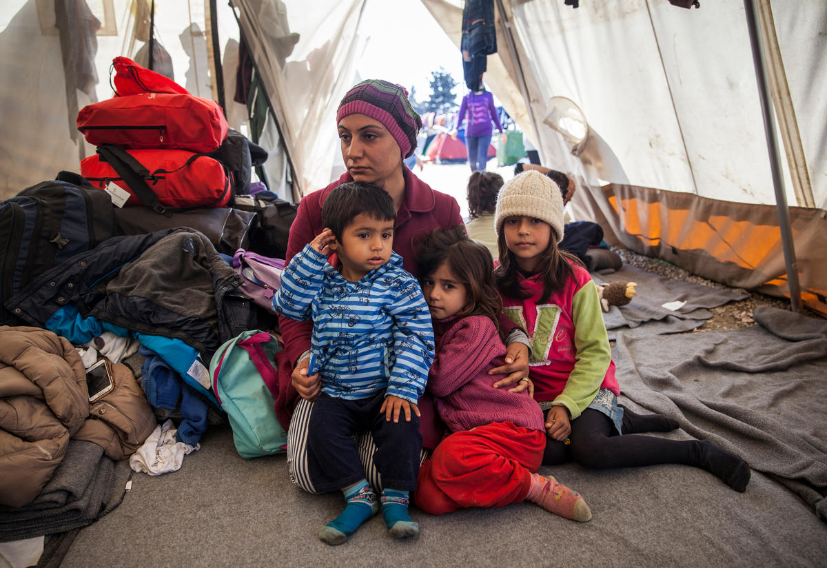 A displaced family inside a tent in a refugee settlement
