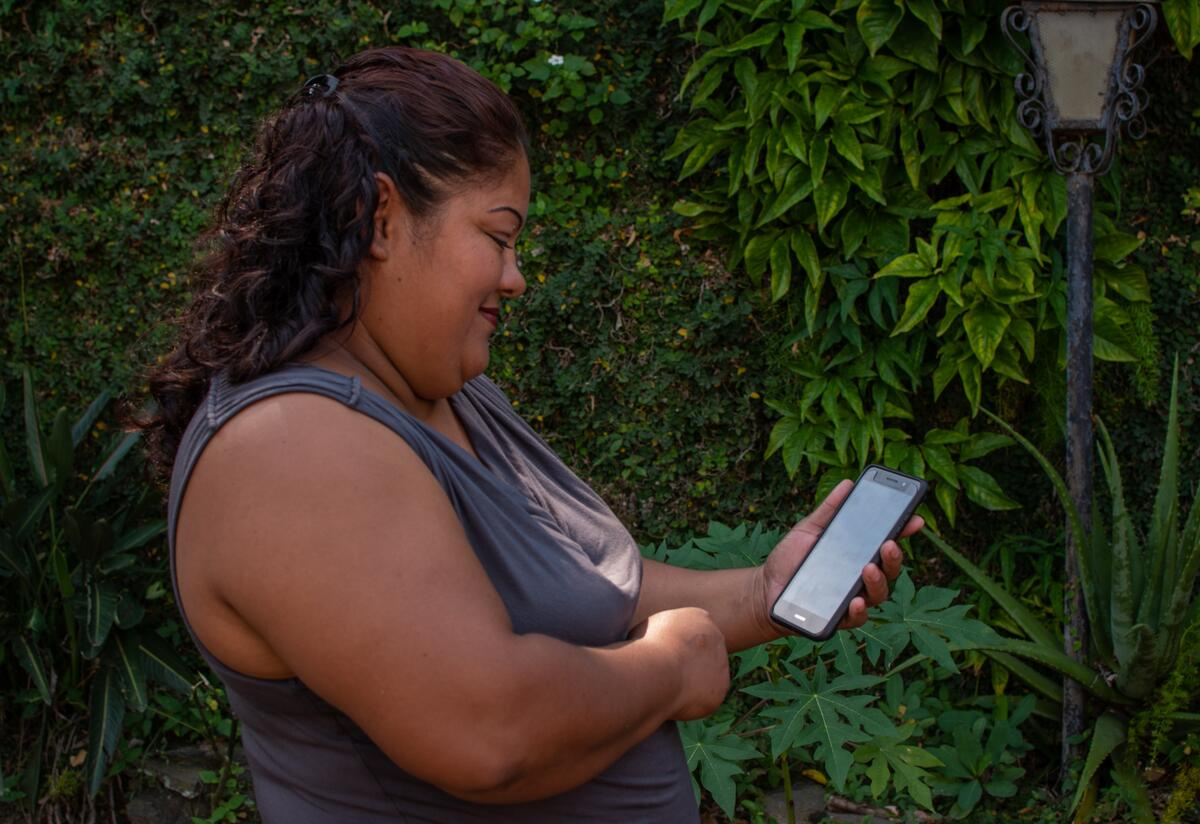 A woman in El Salvador looks at her cellphone