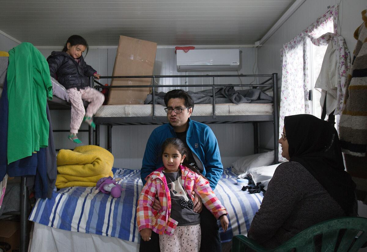 Parents and their two young children in their corrugated iron shelter in Moria refugee camp, Greece