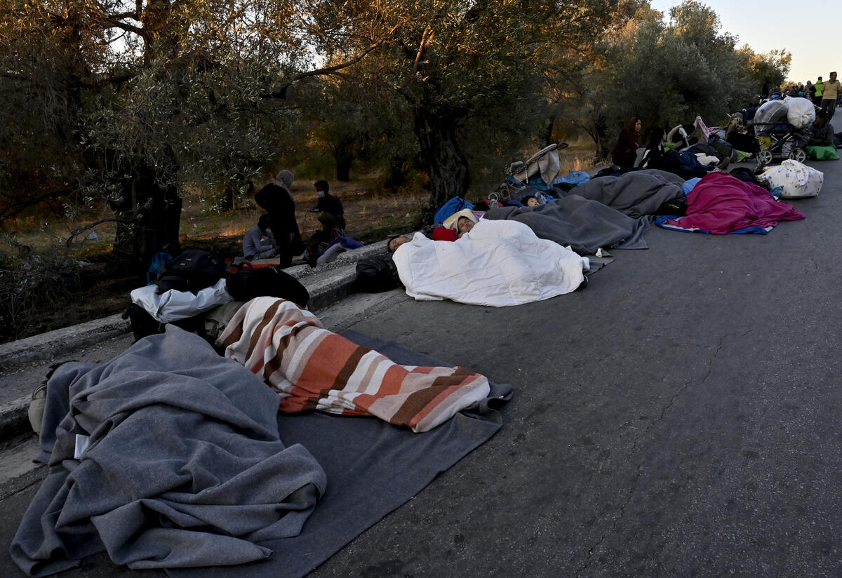 People wrapped in blankets sleep on a road after being displaced by a fire in Moria refugee camp in Lesbos, Greece.