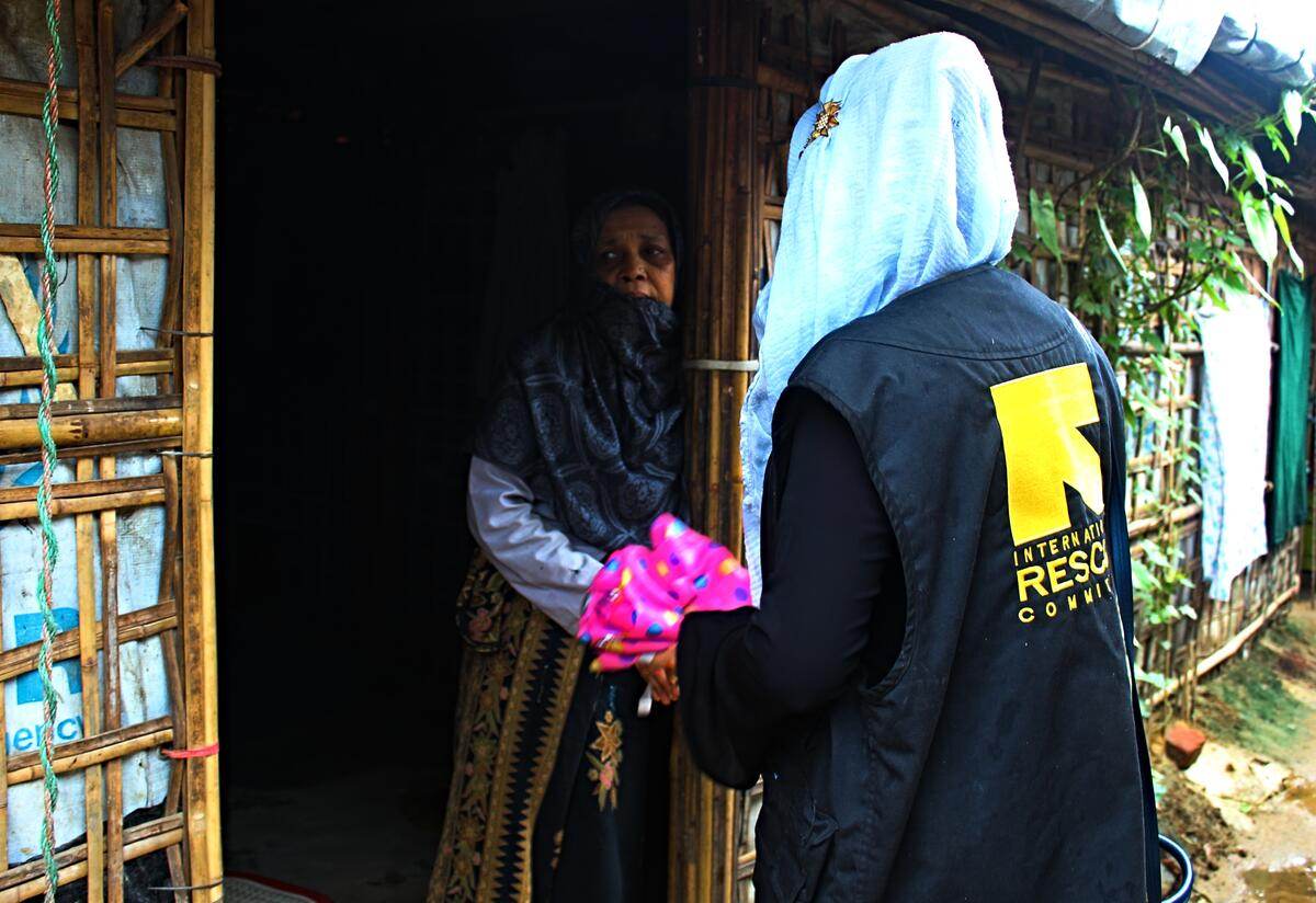 An IRC community volunteer greets a refugee from Myanmar at the door of her makeshift bamboo home in a Bangladesh refugee camp