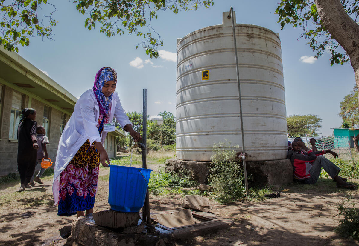 An IRC staff member collects water at a tap in Ethiopia. The IRC is responsing to the Tigray crisis.