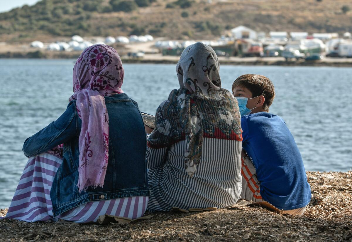 Rahima and two of her children sit together facing the sea in their refugee camp on the Greek island of Lesbos.