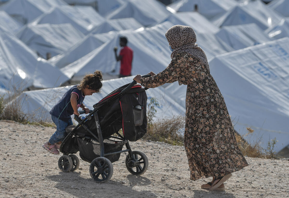 A 33-year-old Syrian refugee, wearing a face mask to protect herself from the coronavirus, pushes two of her children in a stroller past rows of tents in a crowded refugee camp on the Greek island of Lesbos.