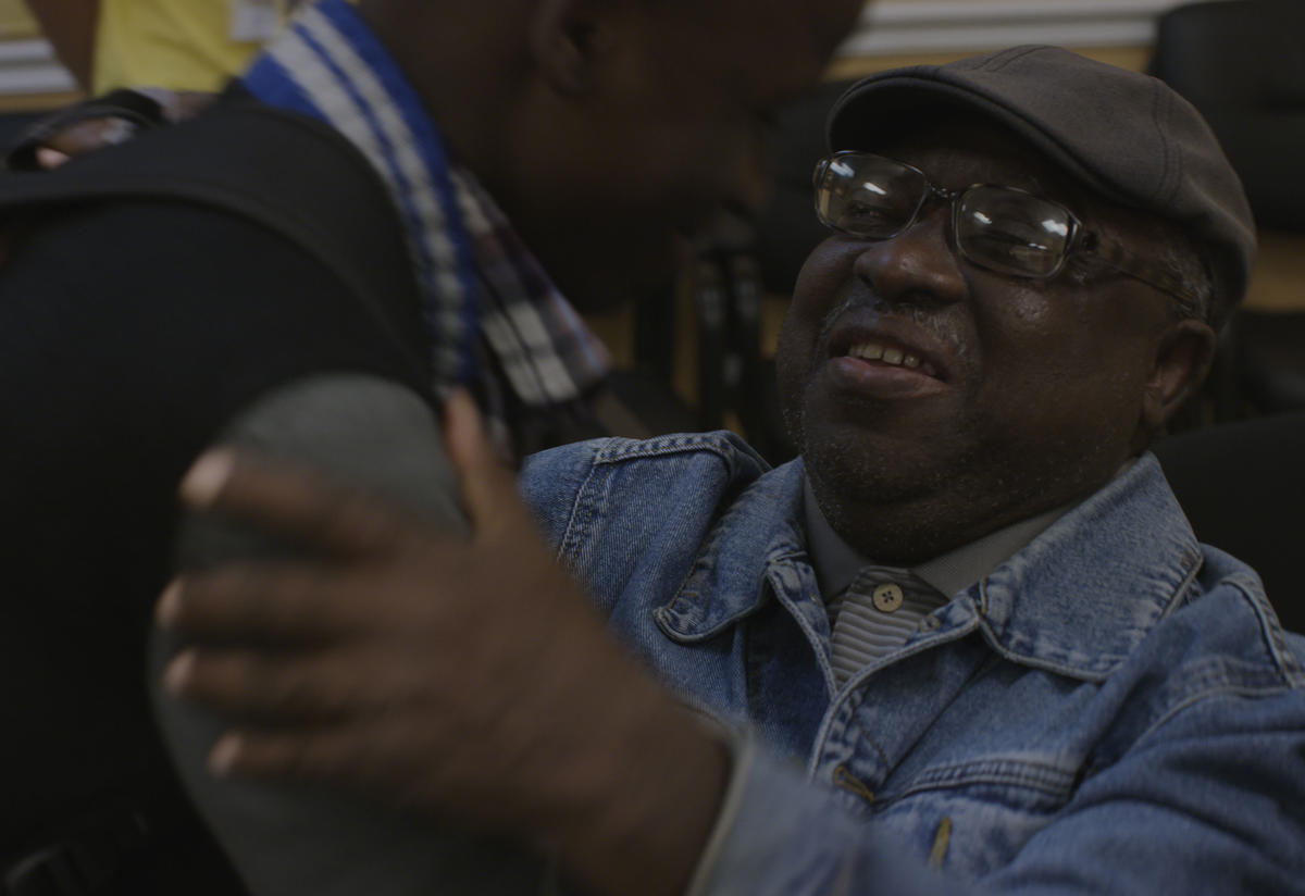 Mawa embraces his young son