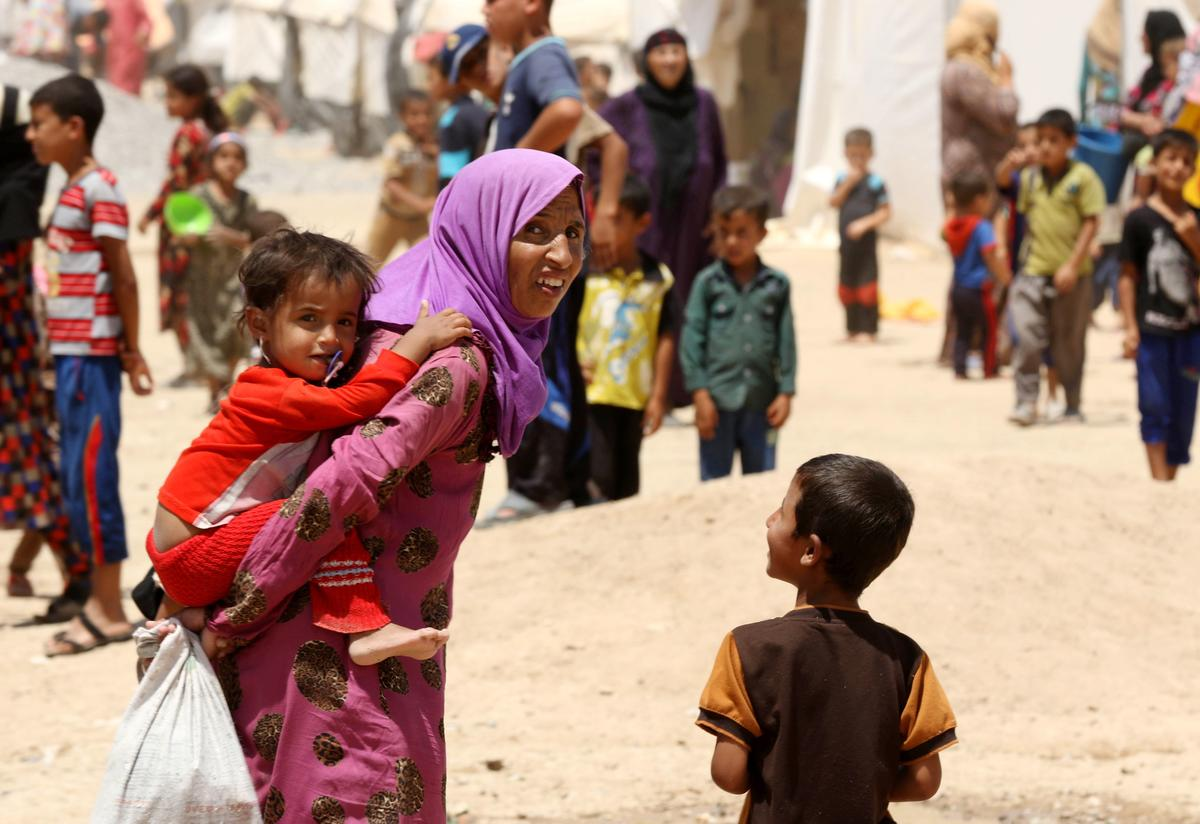 Iraqi displaced women and children, who fled the violence in the northern city of Mosul, walk at the Dibaga camp on July 16, 2016 in Makhmur, about 280 kilometres (175 miles) north of the capital Baghdad.
