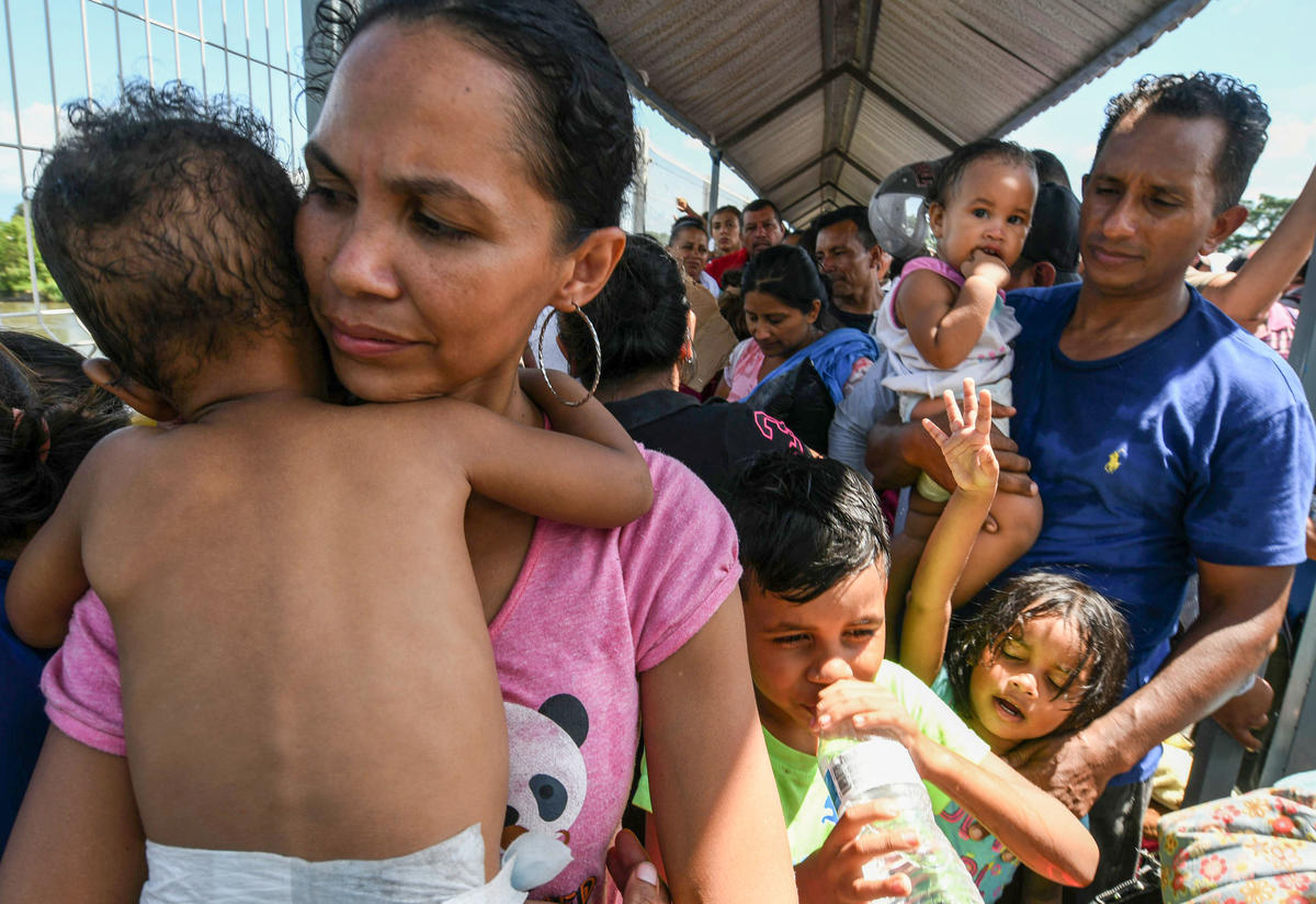 A Honduran migrant couple and their five kids taking part in a caravan heading to the U.S., wait to cross the border from Guatemala to Mexico