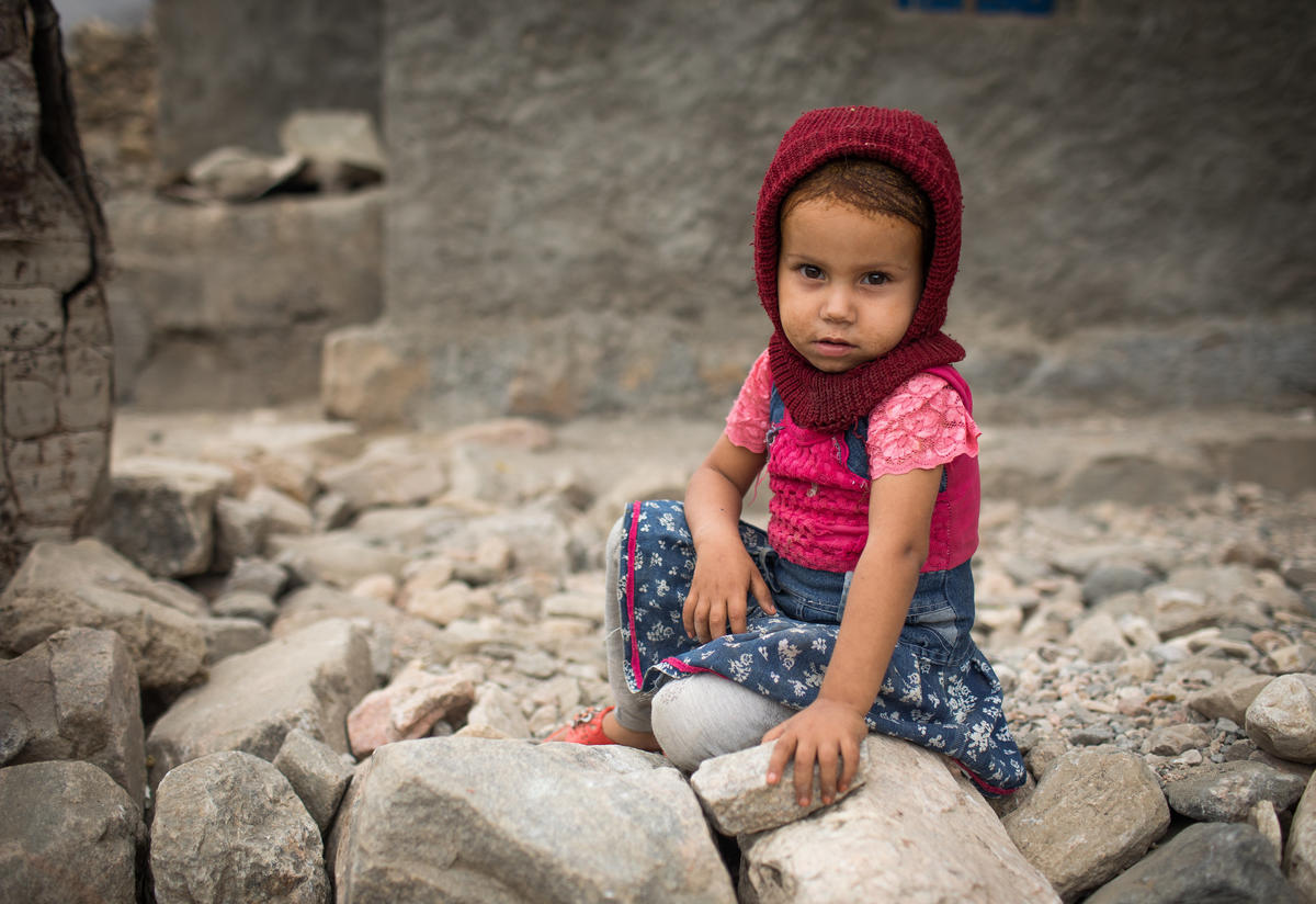 A young girl sits on the ground in a village in Yemen