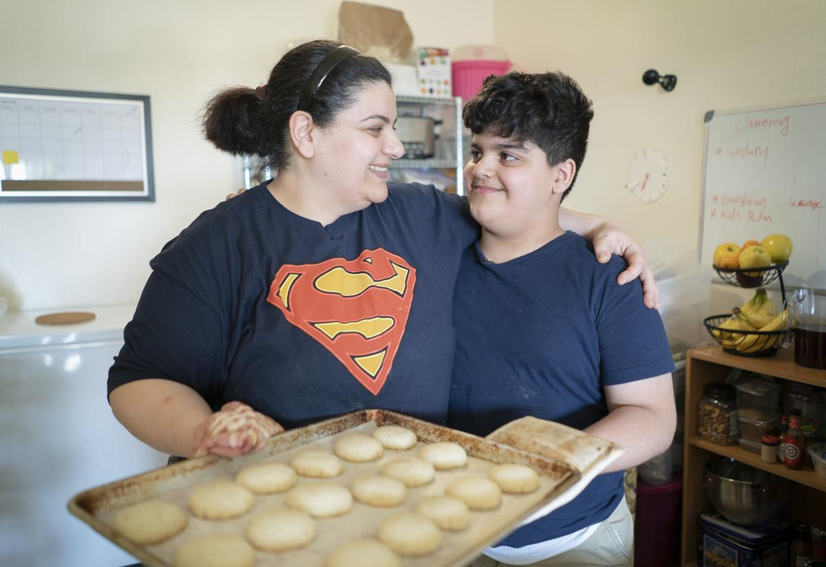 10-year-old Yousif holds a plate of freshly baked shakar lama (caradmom) cookies with his mom, Taghreed
