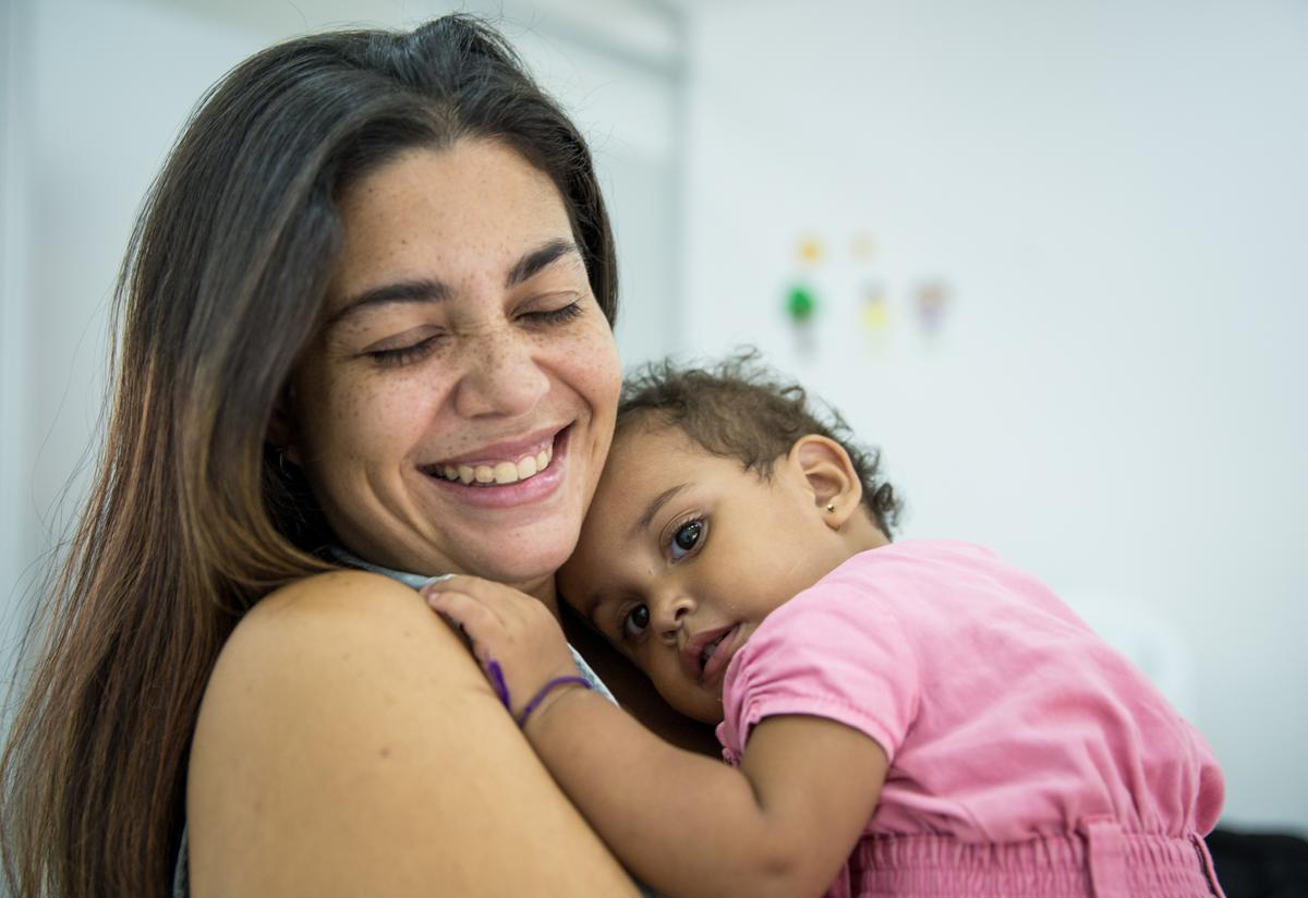 A smiling Andrea holds her sleepy younger daughter at the IRC care center in Cúcuta.